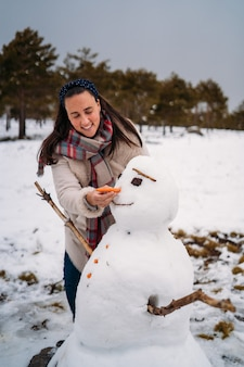 Прекрасная теплая женщина кладет морковный нос на снеговика - концепция отпуска - вертикальное изображение