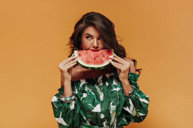 Lovely wavy haired woman in printed white and green outfit looking away and eating watermelon on isolated orange wall