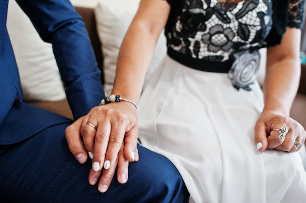 Lovely wedding couple sitting and holding hands with rings on them. closeup photo.