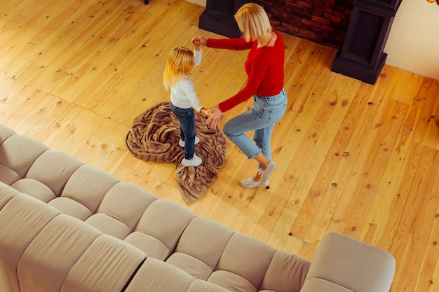 Прекрасных выходных. довольная молодая женщина, держащая за руки своего ребенка, стоя в полу-положении