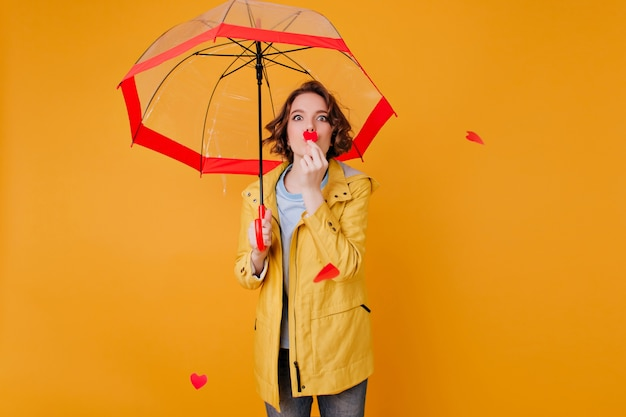 Lovely white female model holding little paper heart while posing under parasol. indoor photo of carefree girl in yellow jacket relaxing during photoshoot with umbrella.
