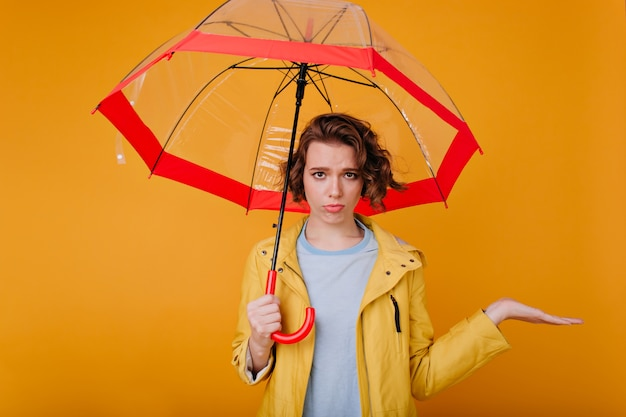 Lovely white girl expressing sad emotions while standing under umbrella. indoor photo of shy upset lady wears autumn attire holding parasol.