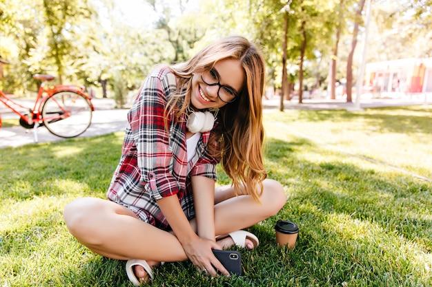 여름 주말에 오싹한 헤드폰으로 사랑스러운 백인 소녀. 잔디에 쉬고 즐거운 백인 여성 모델입니다.