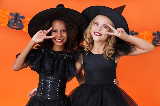 Lovely witch girls in black halloween costumes smiling and gesturing peace sign isolated over orange pumpkin wall