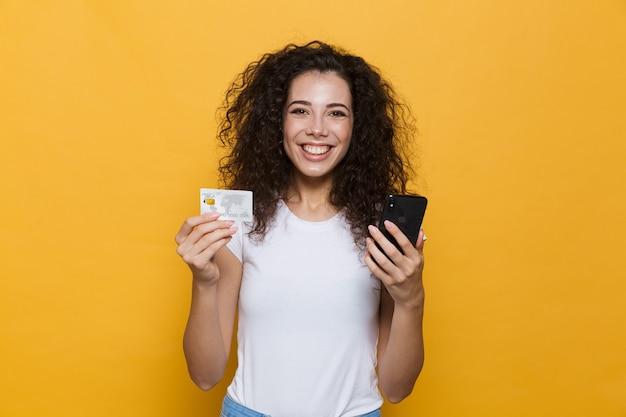 Милая женщина 20 лет в повседневной одежде держит мобильный телефон и кредитную карту, изолированную на желтом