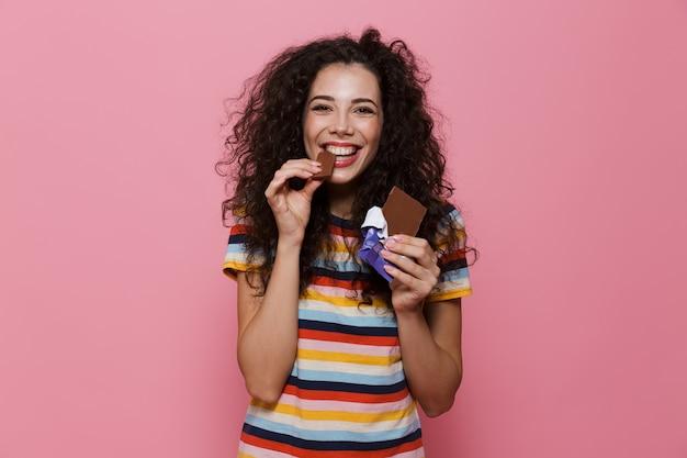 분홍색으로 격리된 초콜릿 바를 먹는 곱슬머리를 가진 20대 사랑스러운 여성