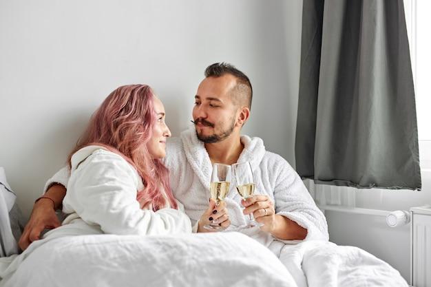 침대에 누워 함께 시간을 즐기고, 함께 음료를 마시고, 사랑, 주말, 휴식 개념을 즐기는 흰 가운에 사랑스러운 여자와 남자