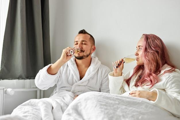침대에 누워 함께 시간을 즐기는 흰 가운에 사랑스러운 여자와 남자