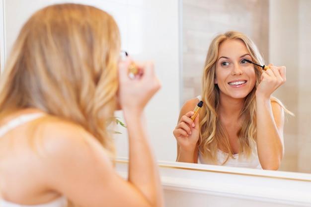 Bella donna che applica mascara davanti allo specchio