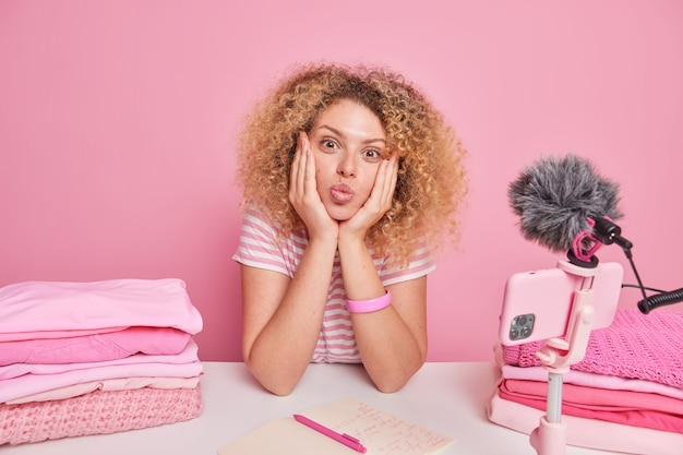Lovely woman blogger keeps lips folded hands on face sits at table near smartphone on tripod records video for blog does domestic work poses near piles of folded laundry isolated over pink wall