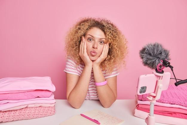 사랑스러운 여성 블로거는 스마트폰 근처 테이블에 손을 대고 삼각대에 앉아 블로그를 위한 비디오를 녹화하며 분홍색 벽에 격리된 접힌 세탁물 더미 근처에서 가사를 하고 있습니다.