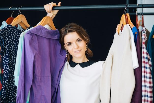 Donna adorabile dietro la rotaia dei vestiti