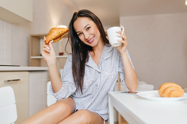 Lovely woman in cute blue pajama posing with smile during breakfast in cozy room