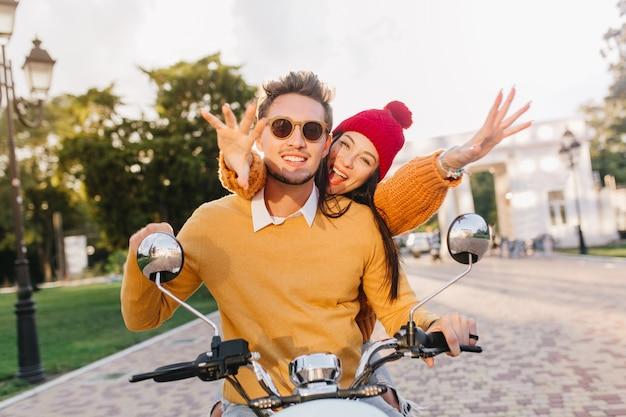 Bella donna in cappello rosso carino agitando le mani godendo di un appuntamento estremo con il fidanzato