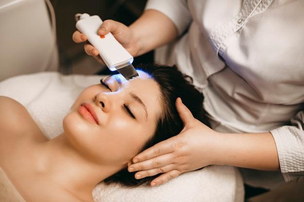 目を閉じてスパベッドに寄りかかって顔に超音波処理をしている素敵な女性。