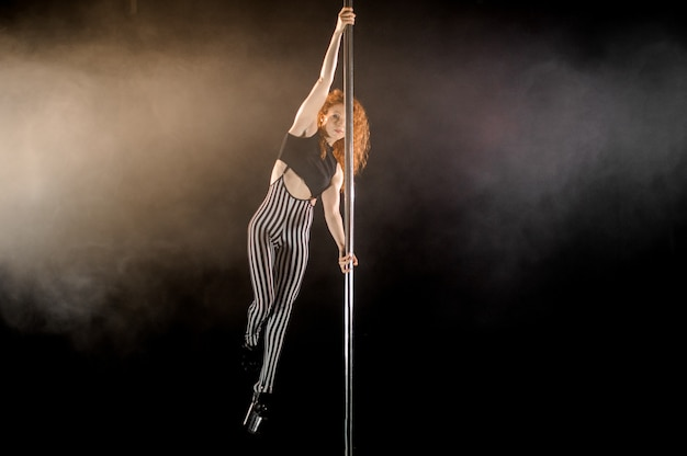 Lovely woman exercises pole dance in the smoke against a black background