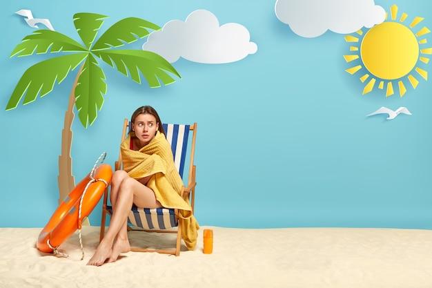 素敵な女性は海で泳いだ後、寒さを感じ、ヤシの木の近くのデッキチェアに座っています
