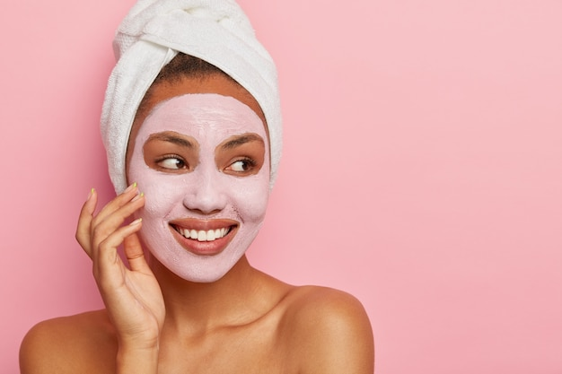 Lovely woman has delicate sooth skin, wears cream mask on face to reduce acnes, has healthy complexion, hygienic treatments wears white wrapped towel on head