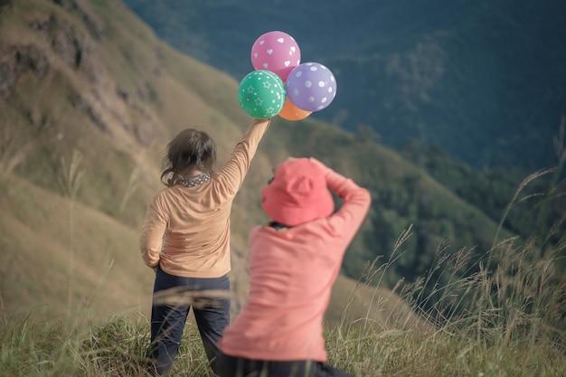 カラフルな風船を持った素敵な女性と彼女のために写真を撮る写真家