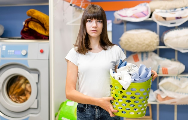 Lovely woman holding green laundry basket