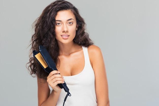 ストレートヘアアイロンを持っている素敵な女性