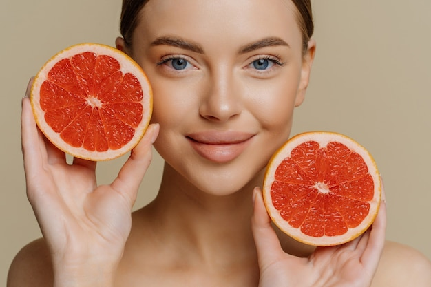 Lovely woman holds halves of grapefruit near face has healthy glowing skin