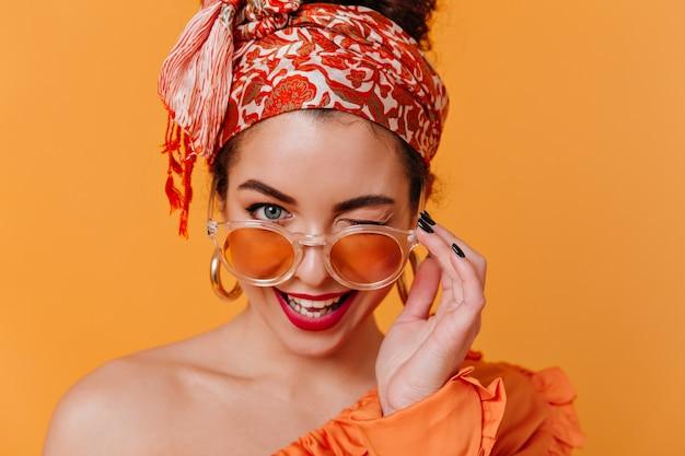 アフリカンスタイルの巨大なイヤリングとヘッドバンドの素敵な女性は、オレンジ色のメガネを外し、コケティッシュにウィンクします。