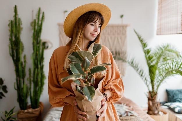 Милая женщина в льняном платье и соломенной шляпе позирует в квартире в стиле бохо