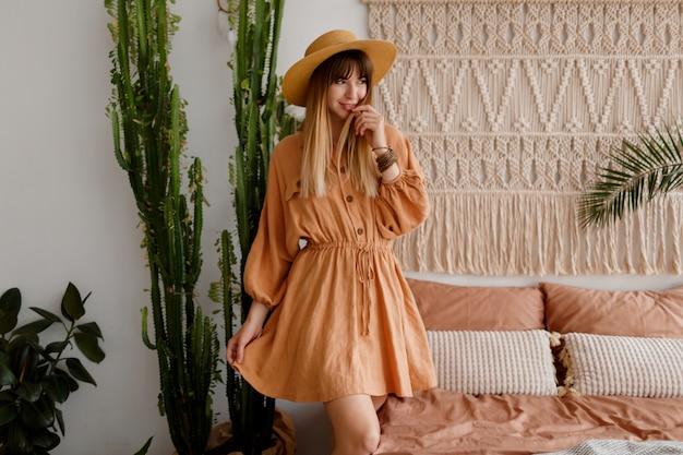リネンのドレスと自由奔放に生きるスタイルのアパートでポーズをとって麦わら帽子の素敵な女性