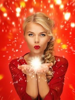 彼女の手のひらの上で何かを吹いている赤いドレスの素敵な女性