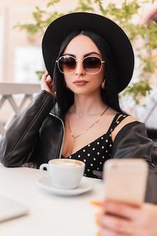 帽子をかぶった黒い革のジャケットのドレスを着たサングラスをかけた素敵な女性がテーブルに座って、屋外のスマートフォンで自分撮りをします。立派な女の子がコーヒーを飲み、晴れた夏の日にカフェで自分の写真を撮ります。