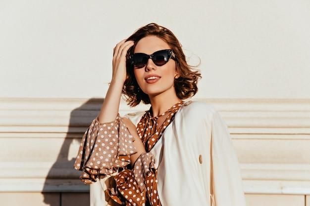 관심을 표현하는 빈티지 복장에 사랑스러운 여자. 선글라스에 매력적인 행복 한 여자의 야외 샷.