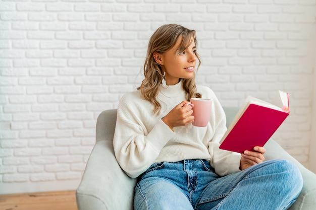 Милая женщина в теплом мягком свитере наслаждается чашкой чая и читает книгу уютным зимним утром