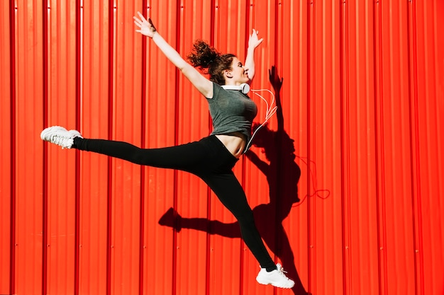 Lovely woman leaping near red wall