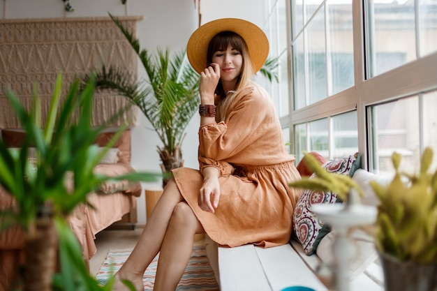 Lovely woman in linen dress and straw hat posing in boho style apartment