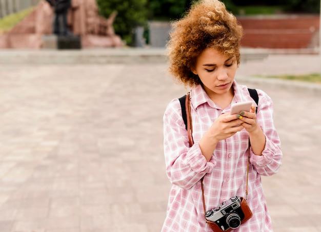 Прекрасная женщина, глядя на свой телефон с копией пространства