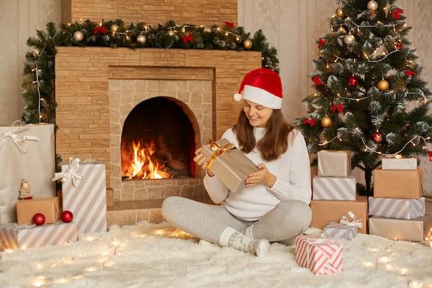 Прекрасная женщина, открывающая подарок на рождество