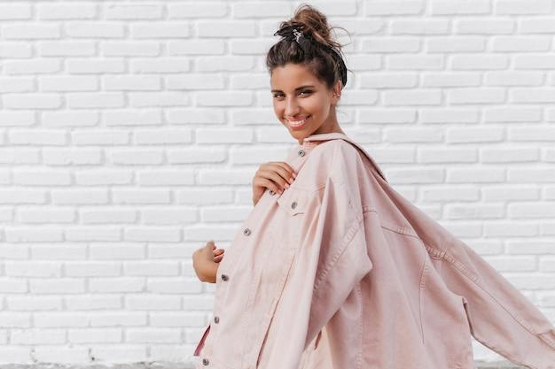 Bella donna in giacca di jeans rosa sorridente e in posa sul muro di mattoni