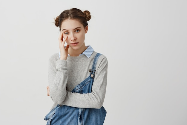 Lovely woman posing with annoyed look being fed up with someone holding her head with hand. girl wearing denim overalls tired of listening uninteresting stories being bored. emotions concept