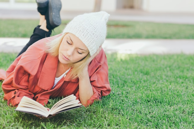 Lovely woman reading book on grass