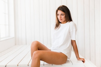 Lovely woman sitting on white surface