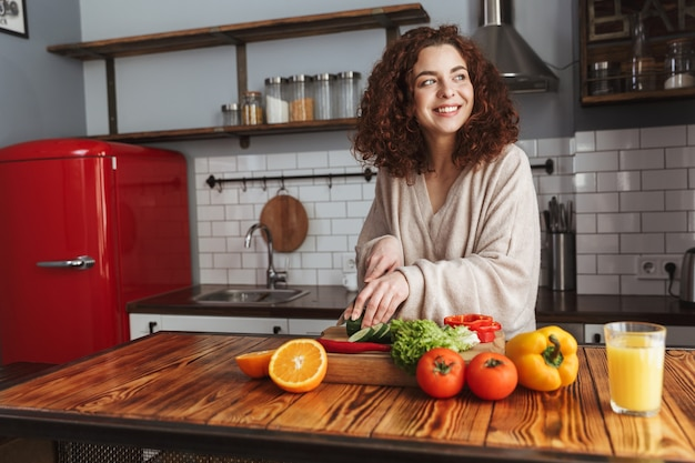 Lovely woman smiling while cooking salad with fresh vegetables in kitchen interior at home