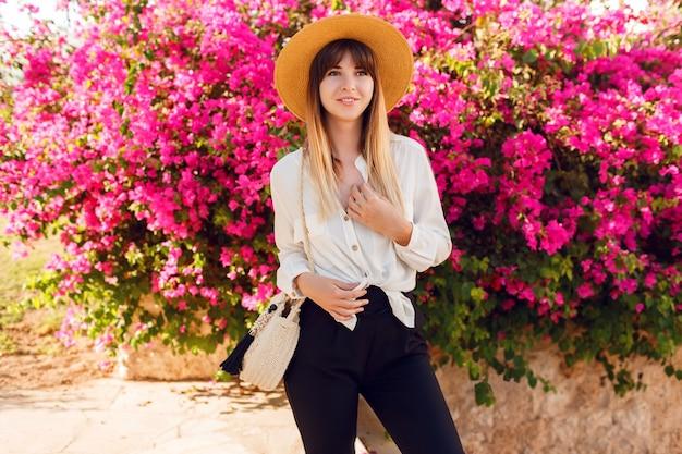 ピンクの花の上に立って素敵な女性麦わら帽子とカジュアルな服を着ています。