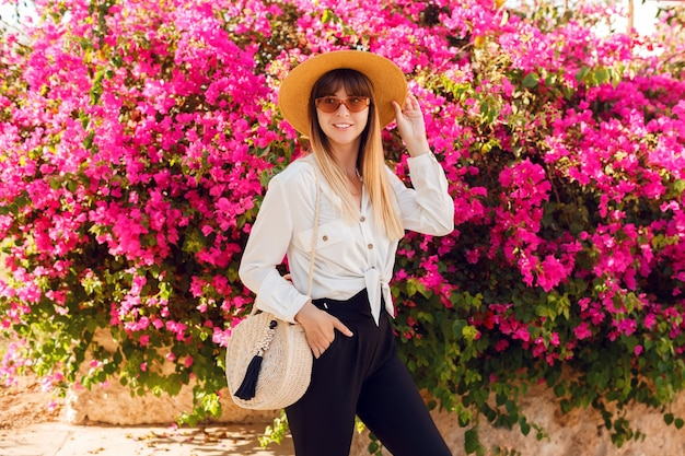 Lovely woman standing on pink flowers wearing straw hat and casual outfit.