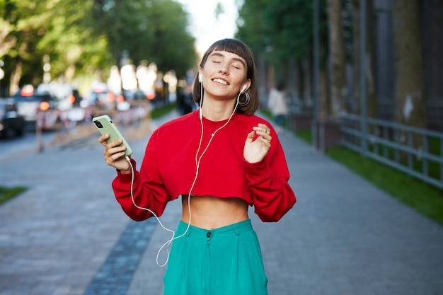 Lovely woman standing on the street with earphones and listen music, cute millenial woman in red stylish sweater holding smartphone and listening music