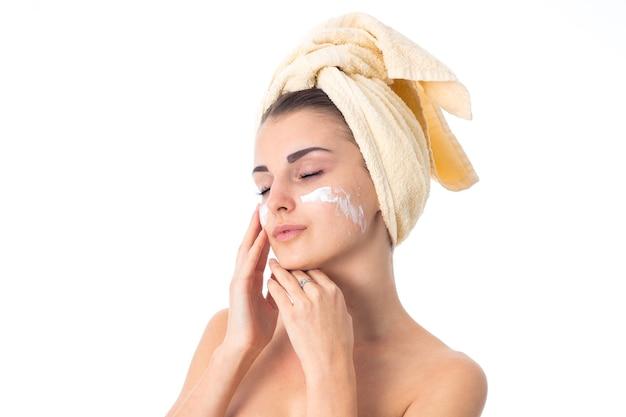 사랑스러운 여자는 흰 벽에 고립 된 크림으로 얼룩진 머리에 수건으로 그녀의 피부를 돌 봅니다.