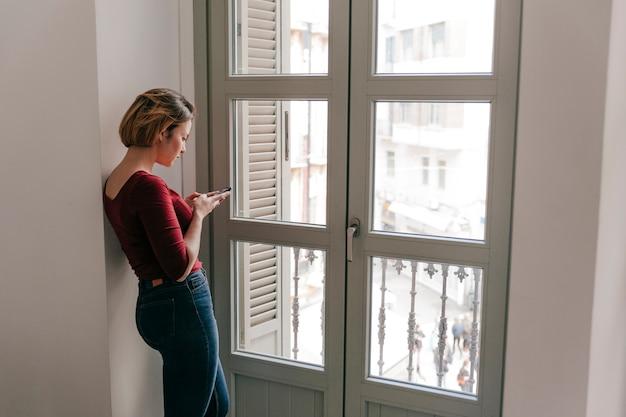Lovely woman using smartphone near window