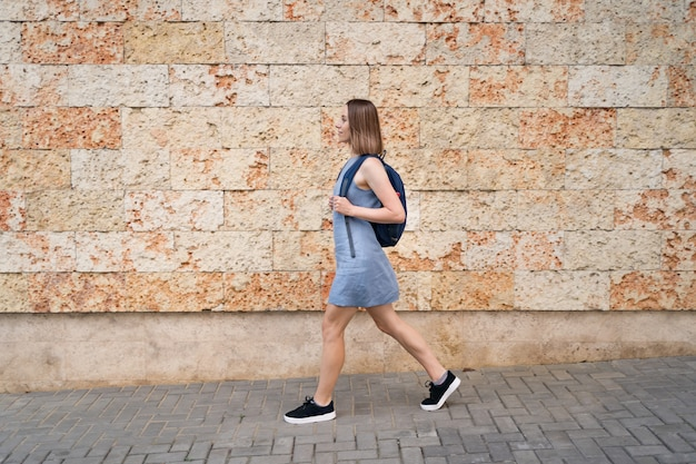 Lovely woman walking with a backpack in blue dress walking in the city on wall decorated with stone with marine texture