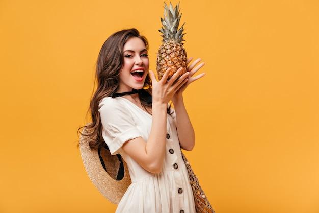 Bella donna in abito bianco con cappello di paglia che tiene ananas su sfondo arancione.