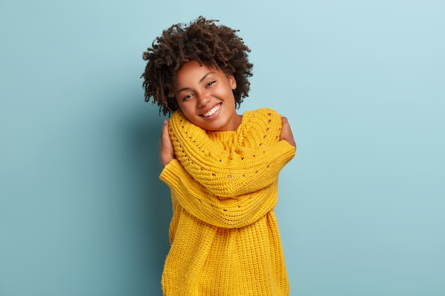Lovely woman with an afro posing in a pink sweater